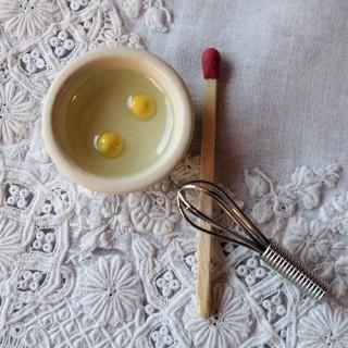 Látigo miniatura con cuenco y 2 huevos rotos.