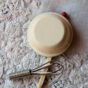 Fouet miniature avec bol et 2 oeufs cassés.
